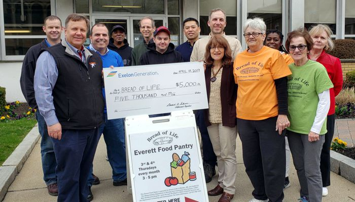 A team of volunteers from Exelon Generation together with staff and volunteers from Bread of Life stand in front of Everett City Hall, the location of Bread of Life's Everett food pantry, as Exelon Generation Northeast Region General Manager Archie Gleason presents $5,000 check to Bread of Life Deputy Director Gabriella Snyder Stelmack.
